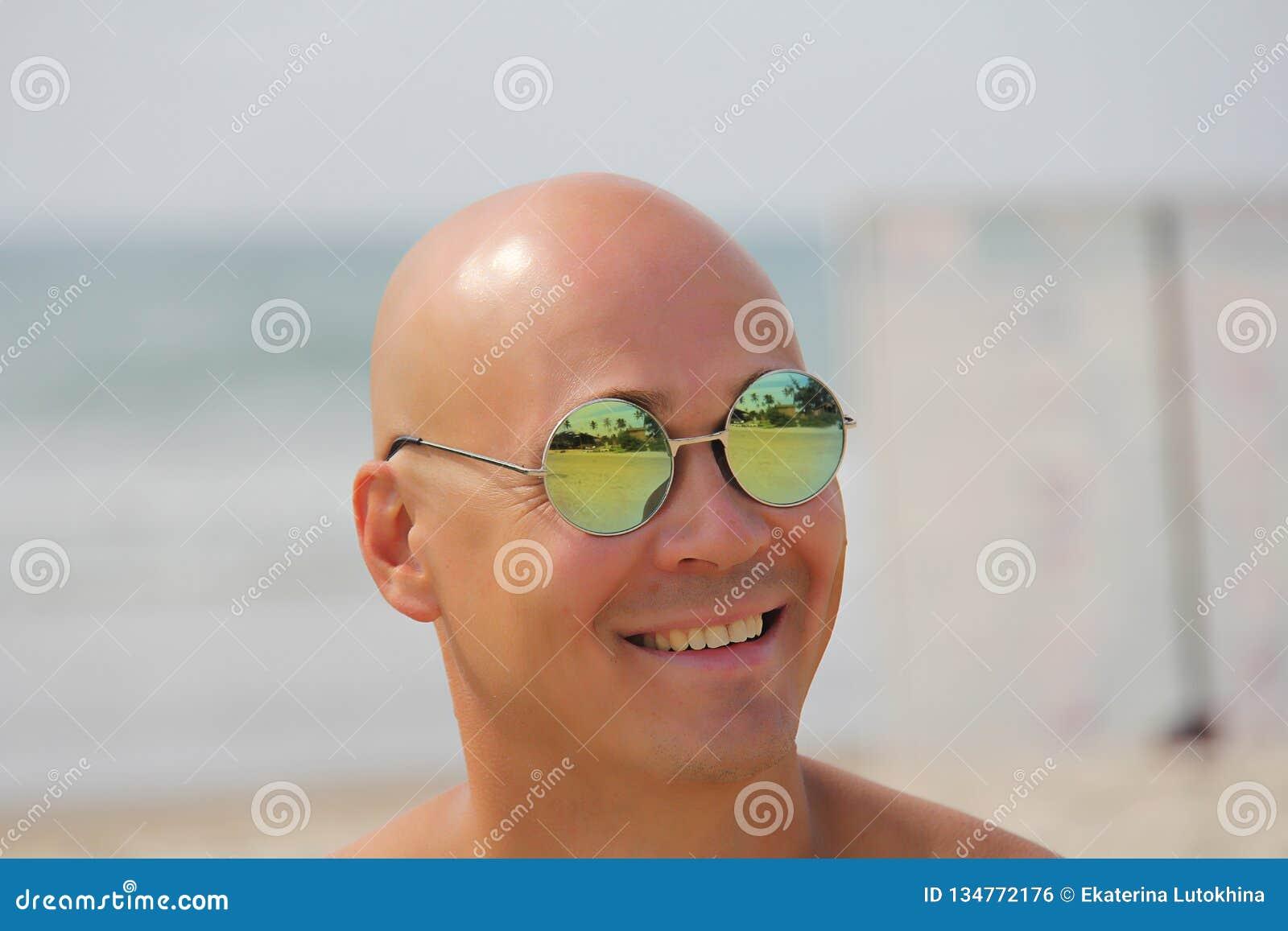 Homme chauve dans des lunettes de soleil de miroir Un bel homme bronzé des vacances, souriant Portrait d un plan rapproché d homm