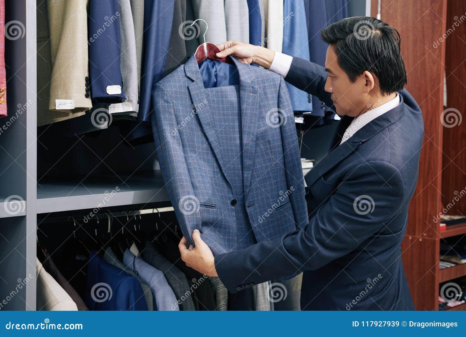 Homme choisissant le costume dans le magasin