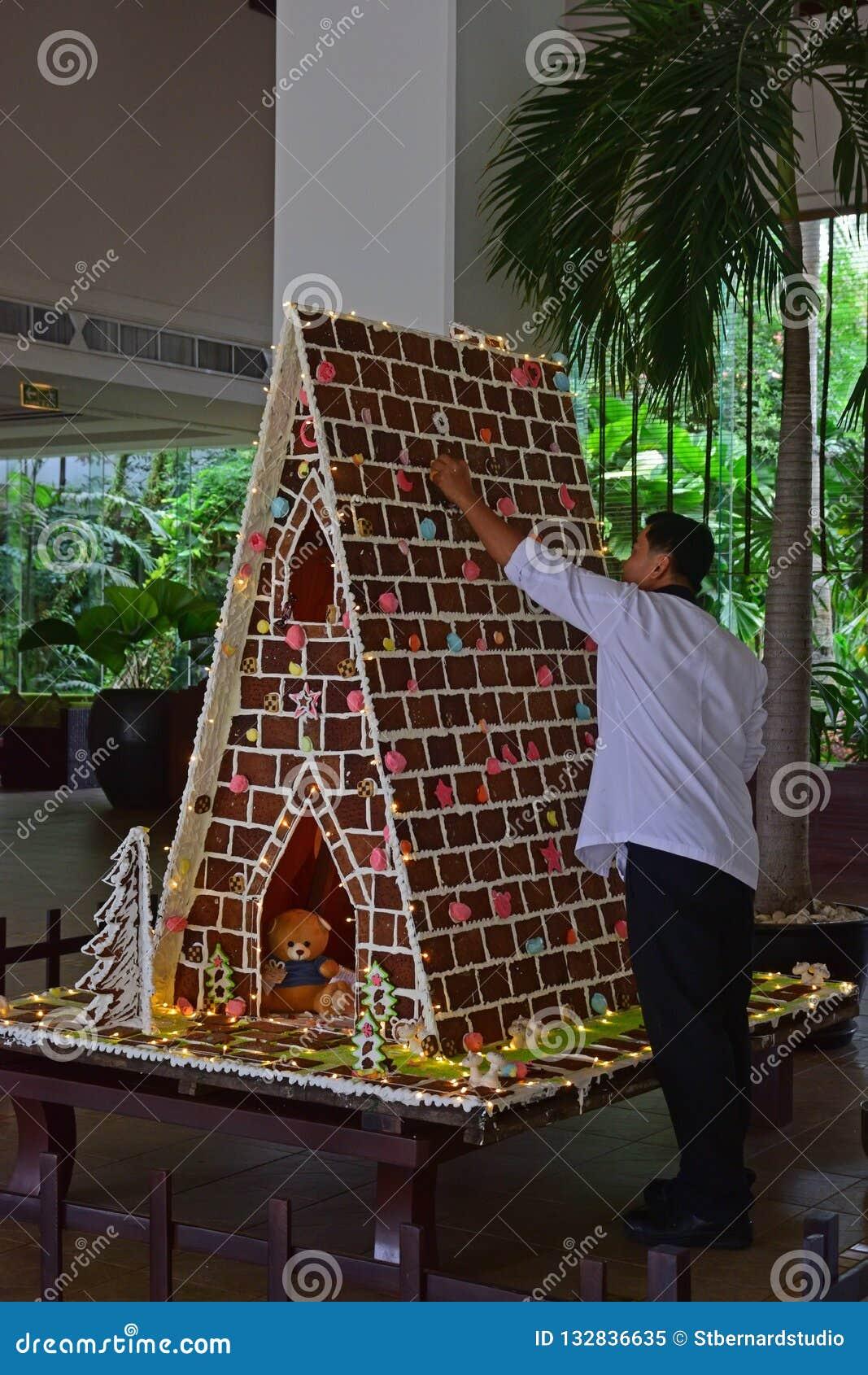 Homme construisant la grande maison de pain d épice dans une installation commerciale