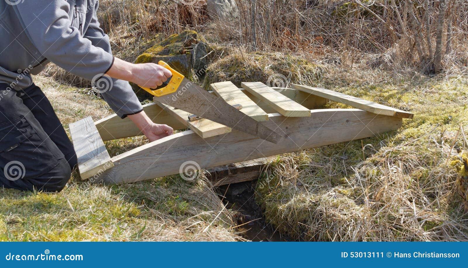Fabriquer Un Petit Pont De Bois homme construisant un petit pont incurvé en bois image stock