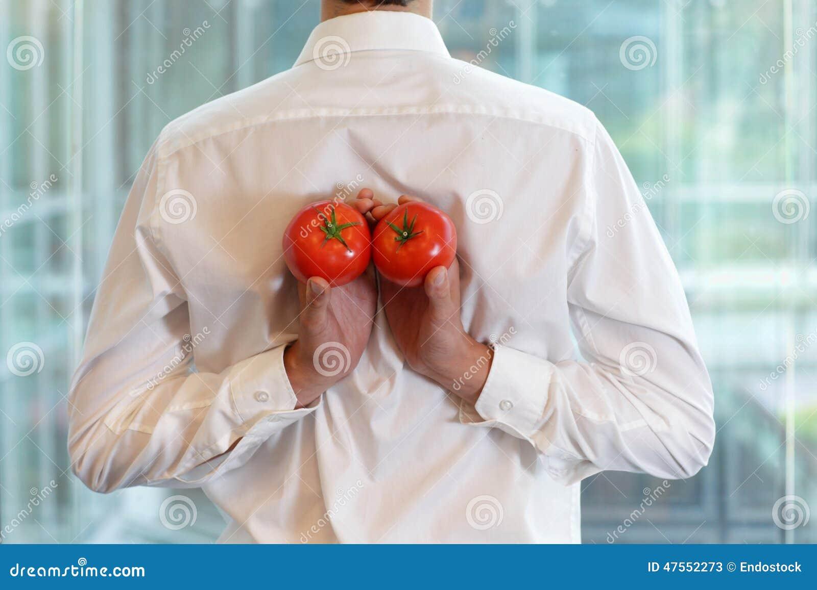 Homme convenable d affaires avec des tomates comme casse-croûte healhy