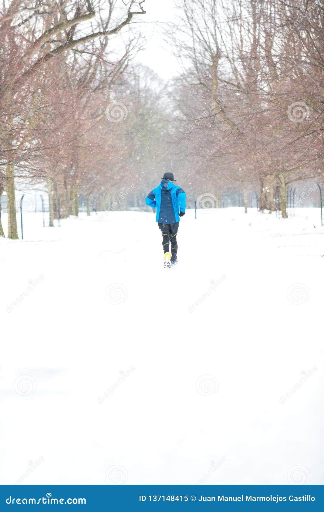 Homme courant dans un jour neigeux