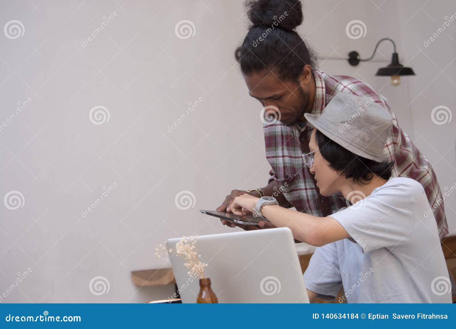 Homme créatif de Young discuter avec l ordinateur portable et le comprimé, le jeune Asiatique et l homme de couleur travaillant a