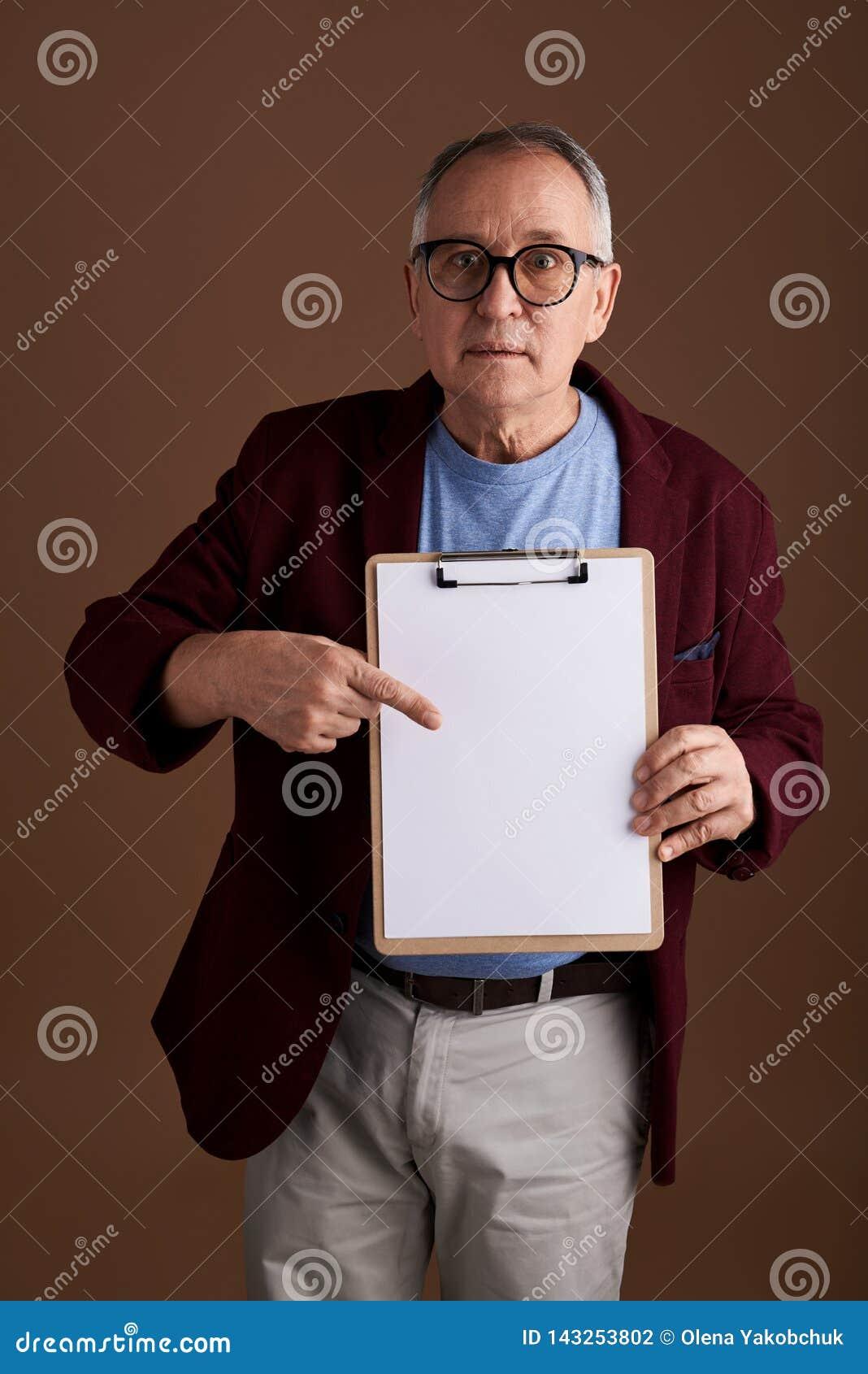 Homme curieux indiquant la feuille de papier et semblant étonné
