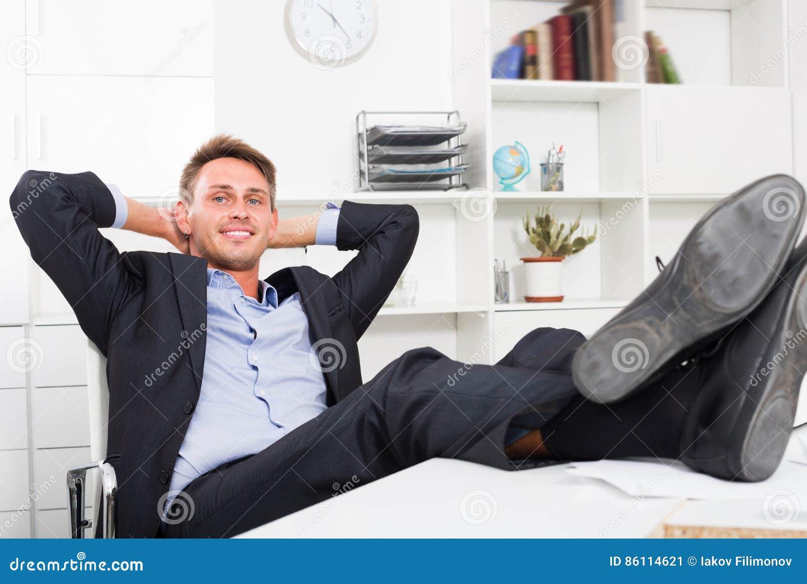 Homme décontracté adulte s asseyant avec des pieds sur le bureau