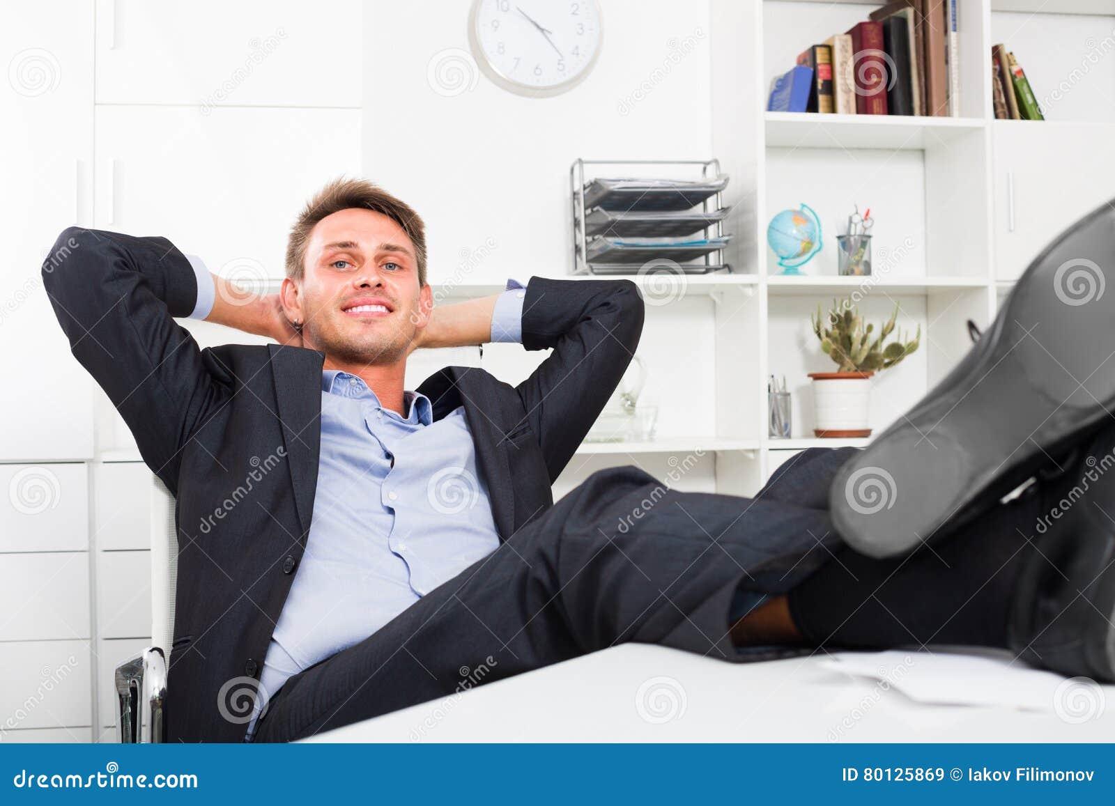 Homme décontracté avec des pieds sur le bureau image stock image