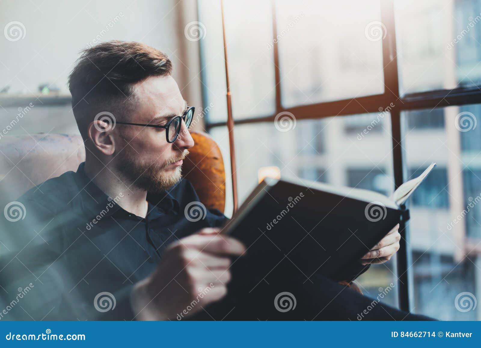 Homme daffaires élégant attirant lisant le livre noir tout en se