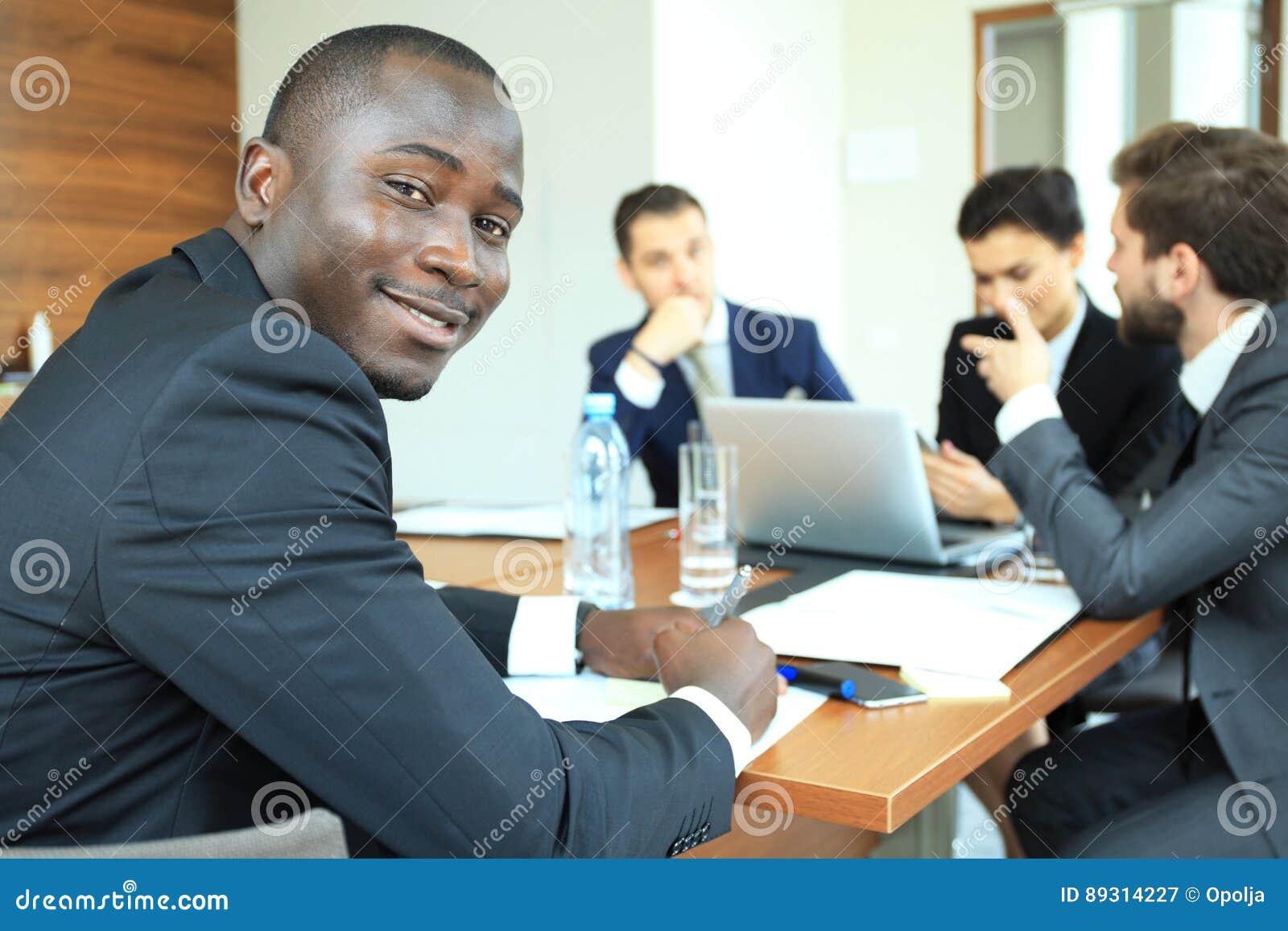 Homme d affaires africain sûr de sourire lors d une réunion avec un groupe de collègues multiraciaux assis à la table de conféren