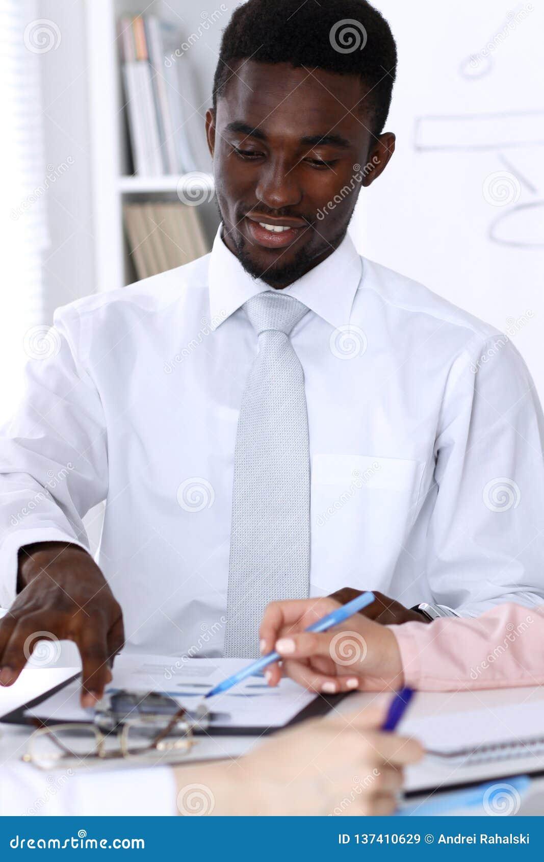 Homme d affaires d afro-américain lors de la réunion dans le bureau, coloré dans le blanc Groupe ethnique multi d hommes d affair