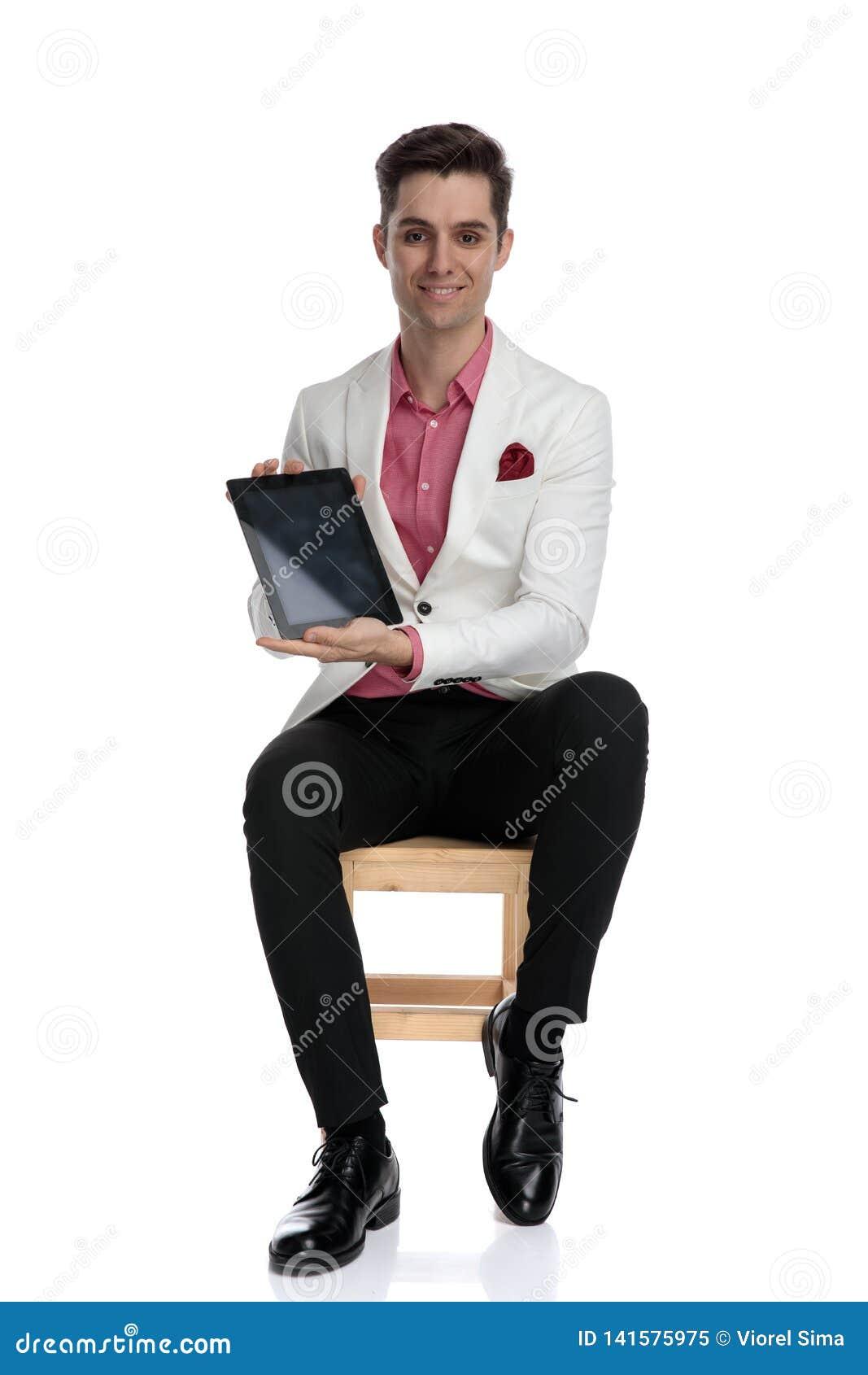 Homme d affaires assis de sourire montrant l écran vide d un comprimé
