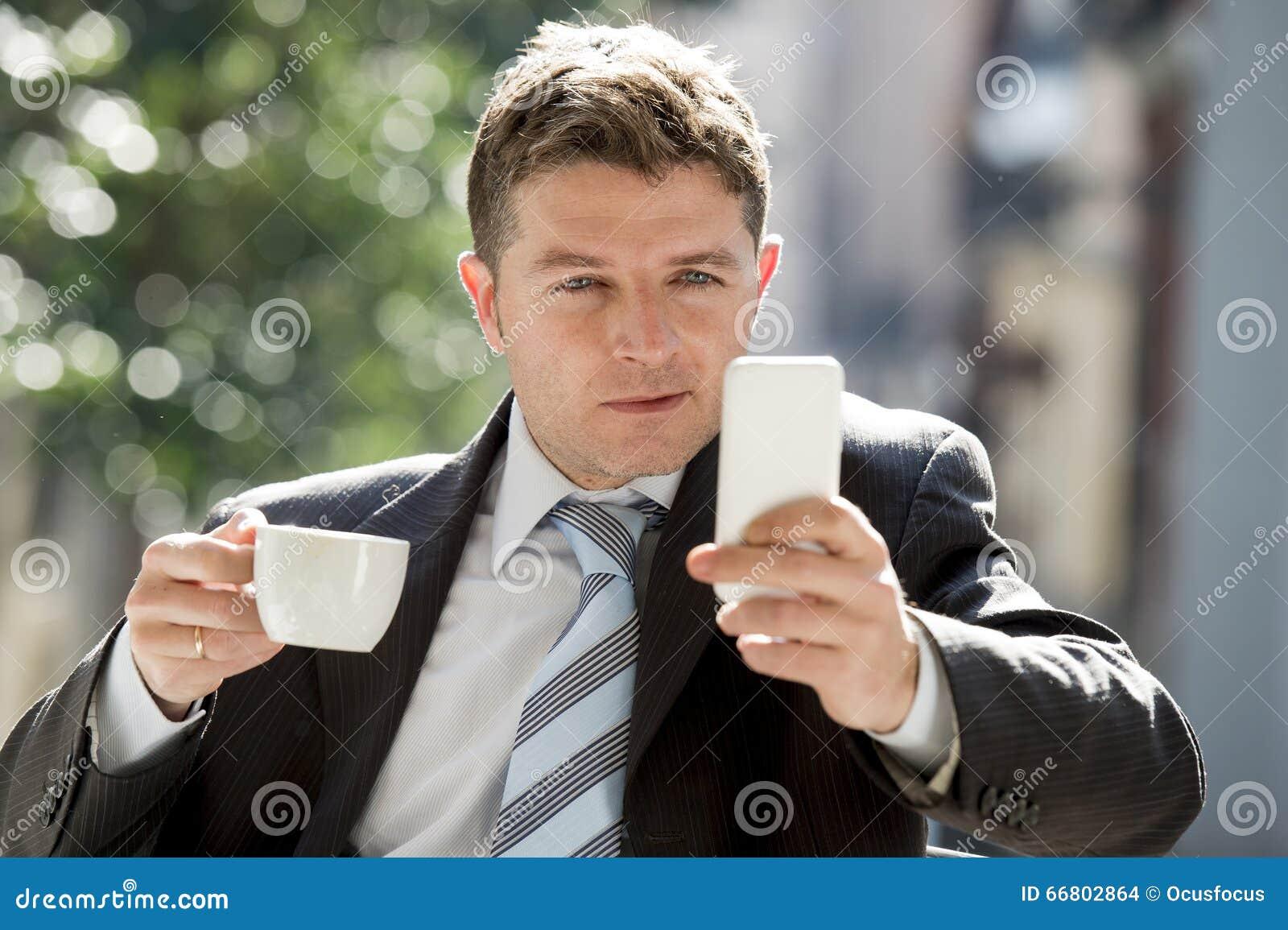 Homme d affaires attirant s asseyant dehors dans la pause-café utilisant le téléphone portable vérifiant des actualités de Ne de