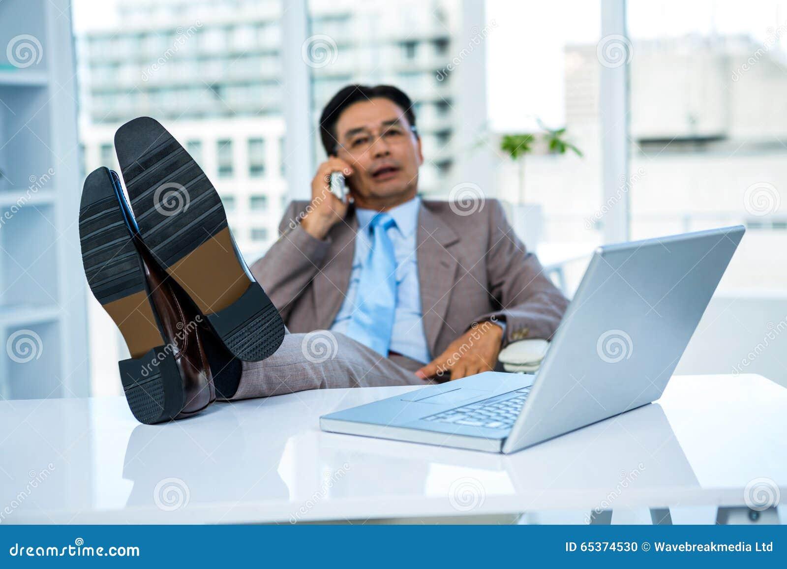 Homme d affaires au téléphone avec ses pieds sur son bureau photo
