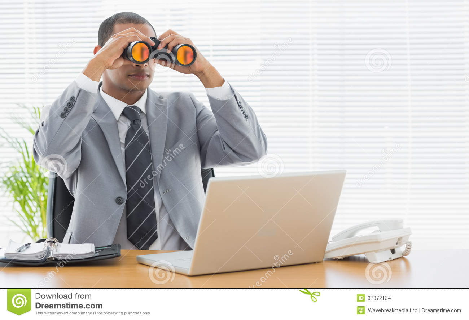 Homme d affaires avec des jumelles devant l ordinateur portable au
