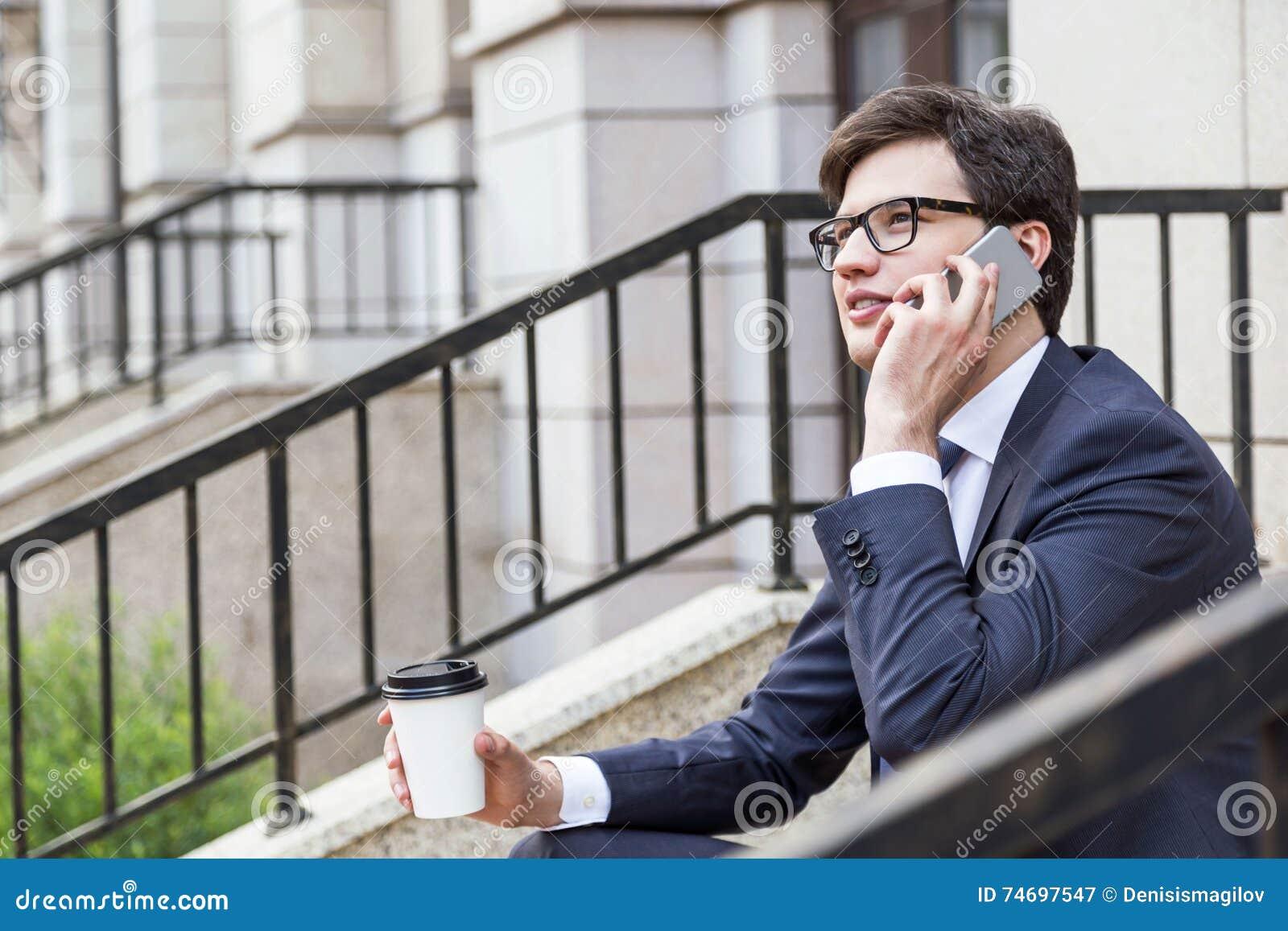 Homme d affaires avec du café au téléphone