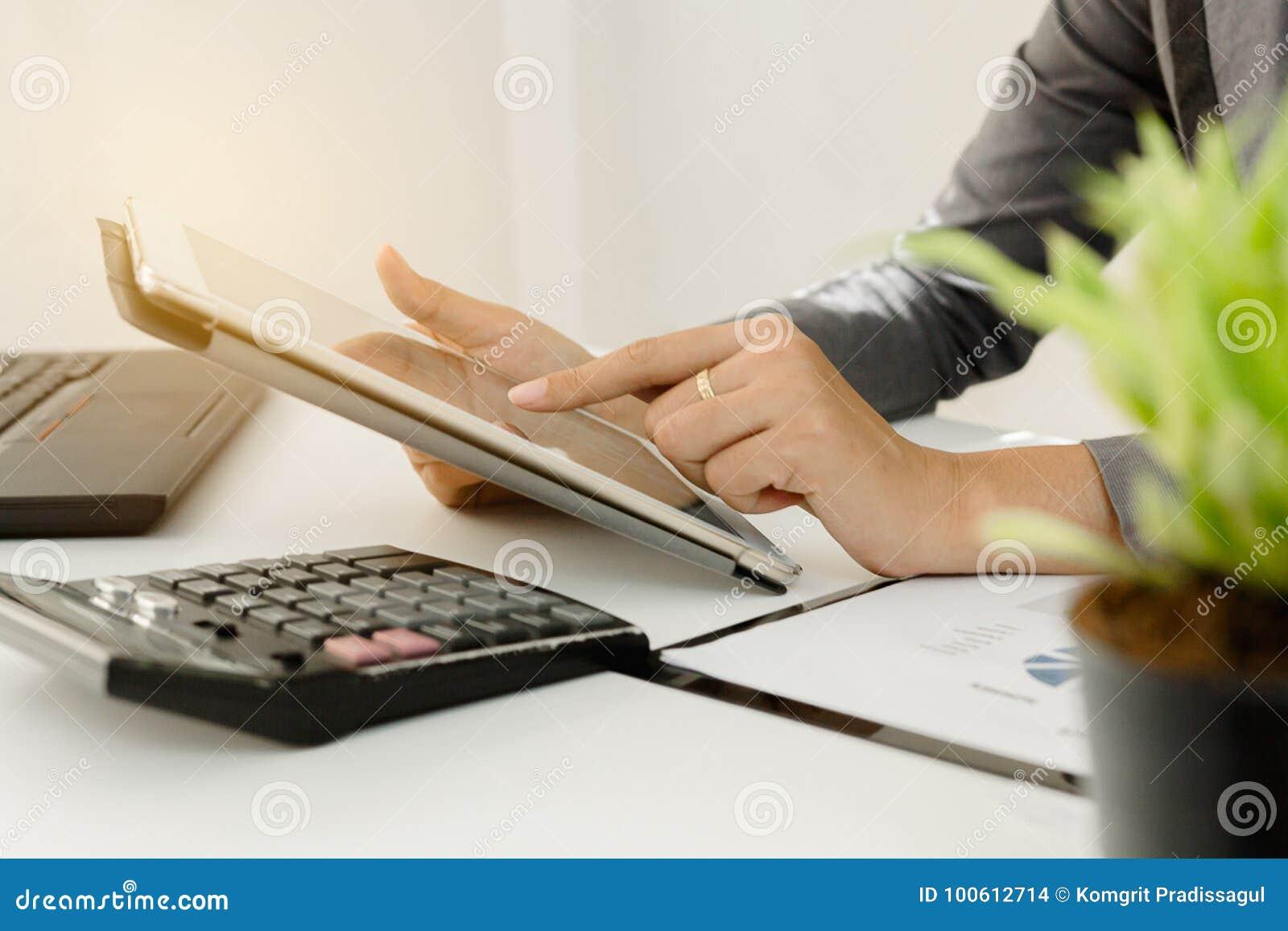 Homme d affaires avec l écran tactile de doigt d un comprimé numérique au bureau sur la table avec des données de graphique de do