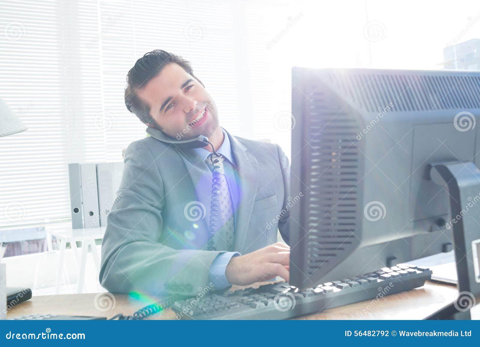 Homme d affaires ayant l appel téléphonique tout en à l aide de son ordinateur