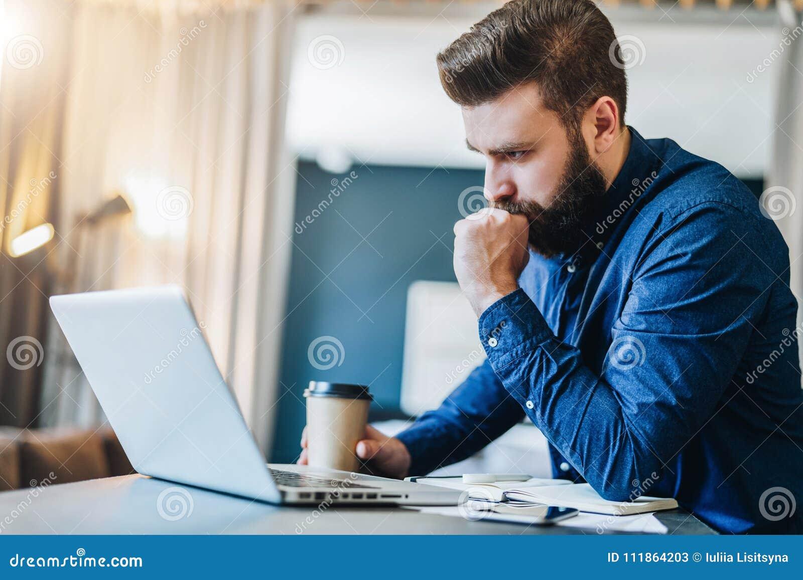 Homme d affaires barbu sérieux travaillant sur l ordinateur, café potable, pensant L homme analyse l information, vérifiant l ema