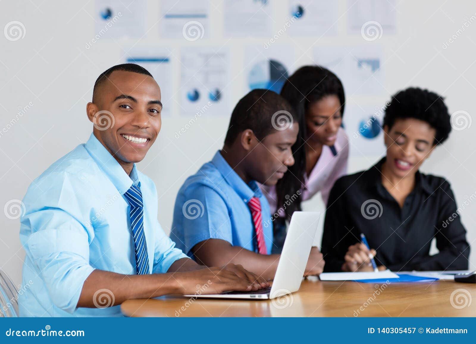 Homme d affaires bel d afro-américain avec l équipe d affaires au bureau