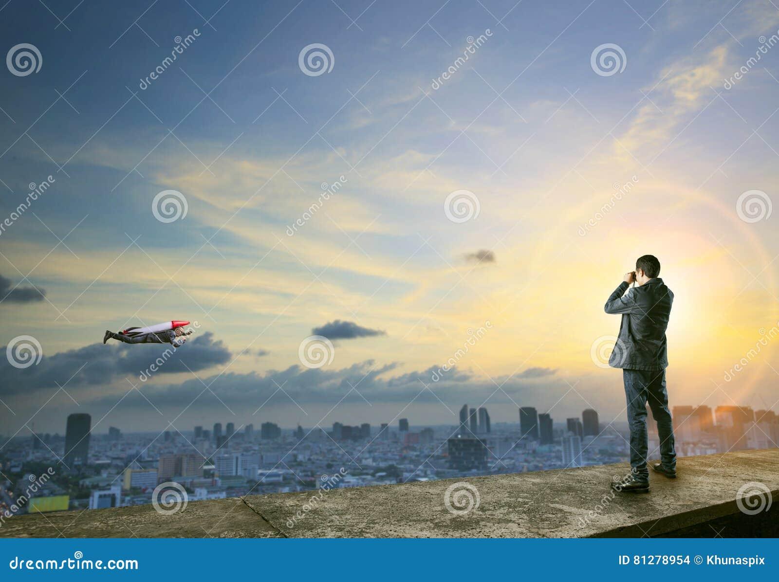 Homme d affaires binoculaire à l homme avec la fusée sur le vol arrière au-dessus de ci