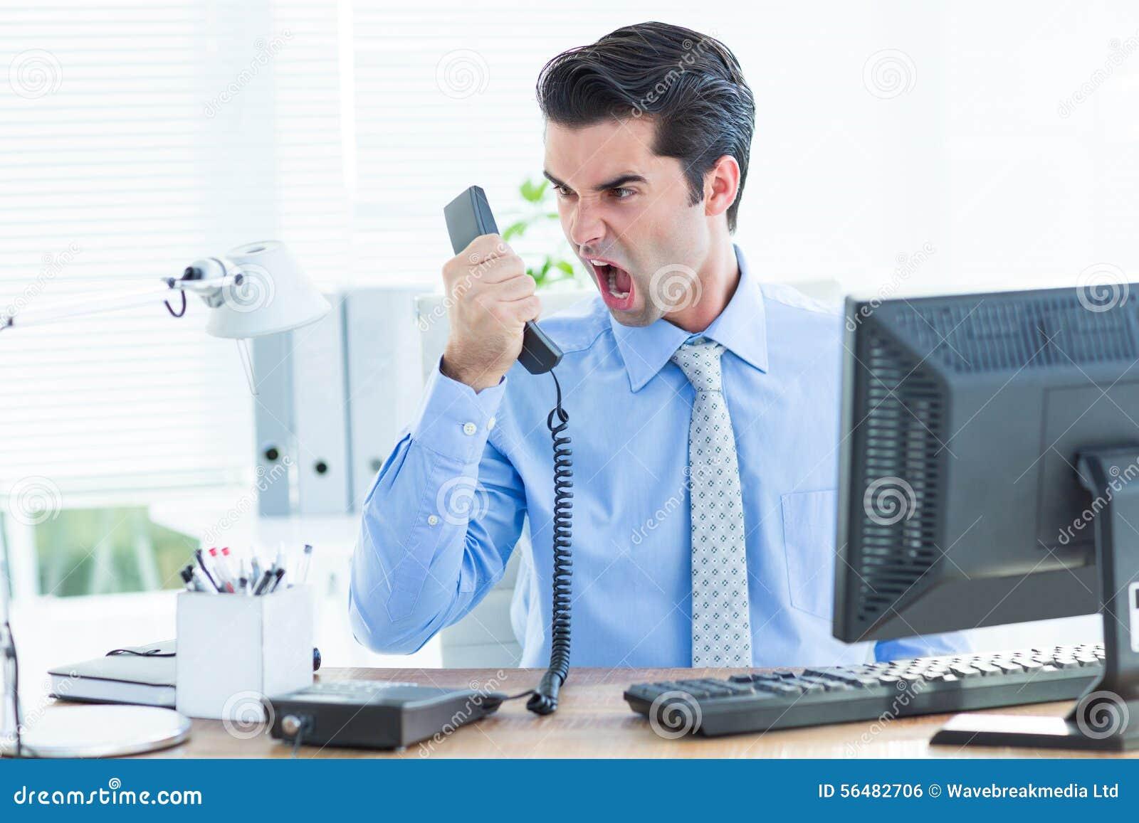 Homme d affaires criant comme il donne le téléphone au bureau