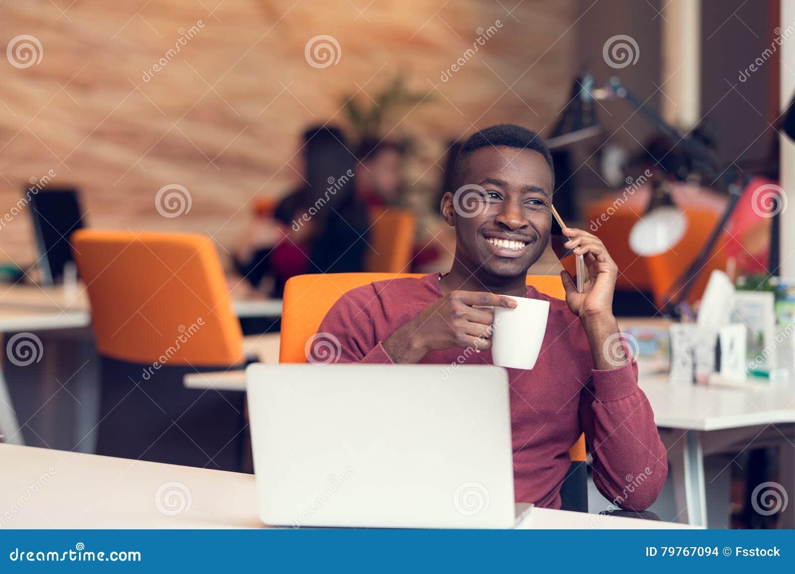 Homme daffaires dafro américain sasseyant à lordinateur dans son