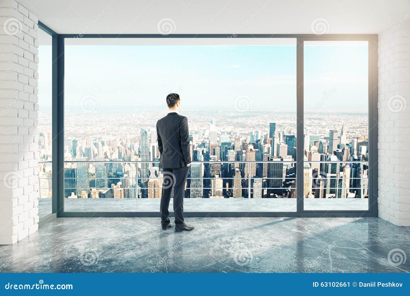 Homme d affaires dans la pièce vide de style de grenier avec le plancher en béton et le CIT