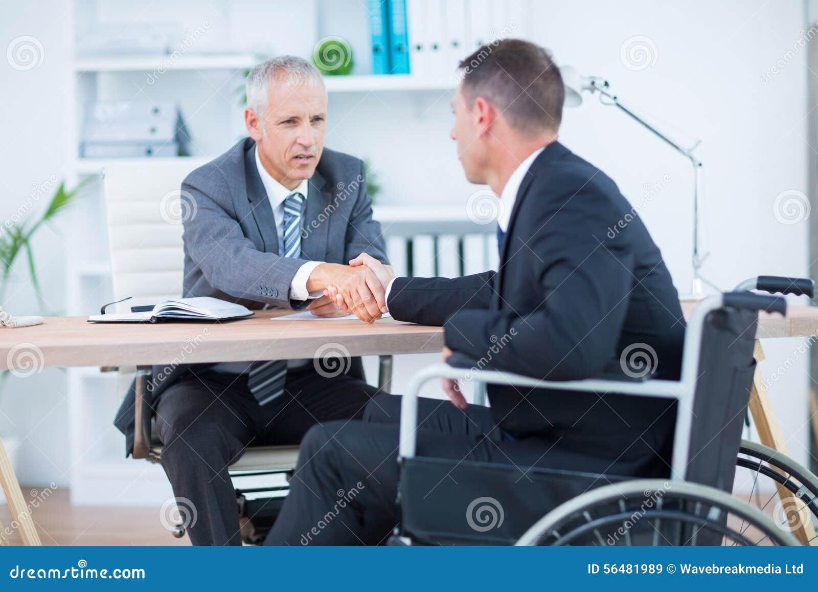 Homme d affaires dans le fauteuil roulant serrant la main au collègue