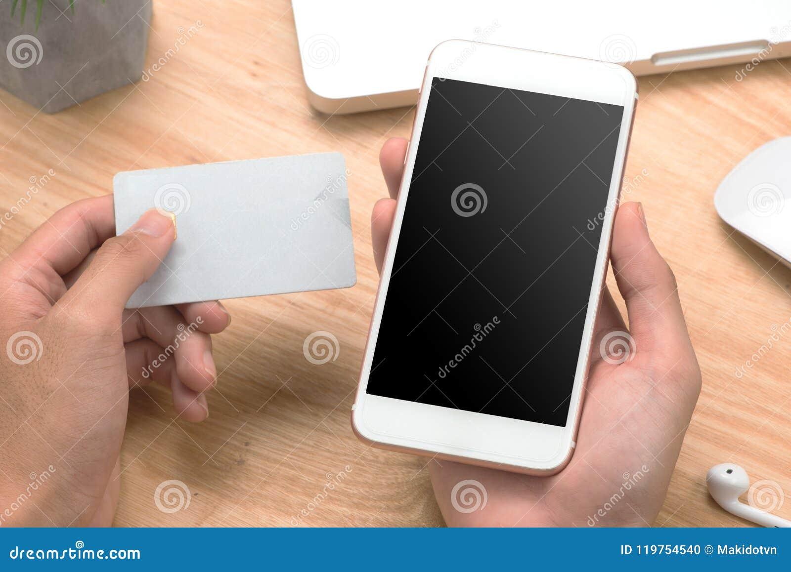 Homme d affaires de photo de plan rapproché tenant la carte de crédit de main et employant le sma