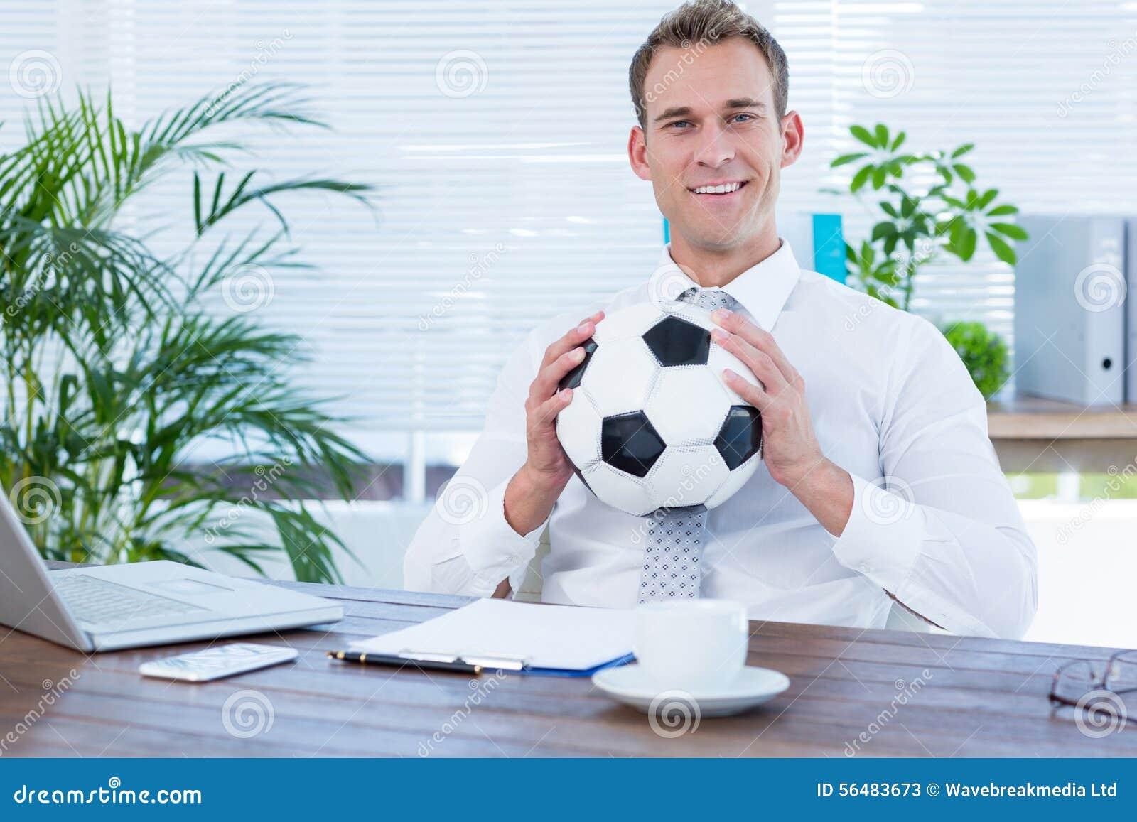 Homme d affaires de sourire retenant un football