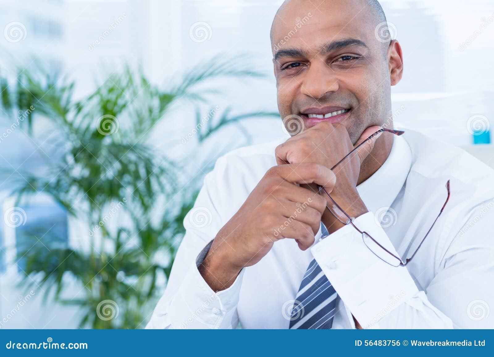 Homme d affaires de sourire tenant des verres de lecture