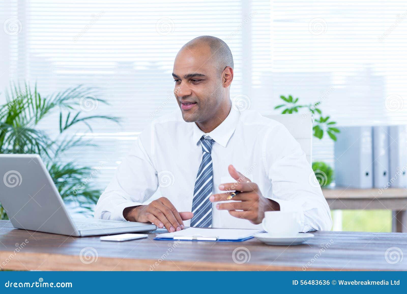 Homme d affaires de sourire travaillant sur l ordinateur portatif