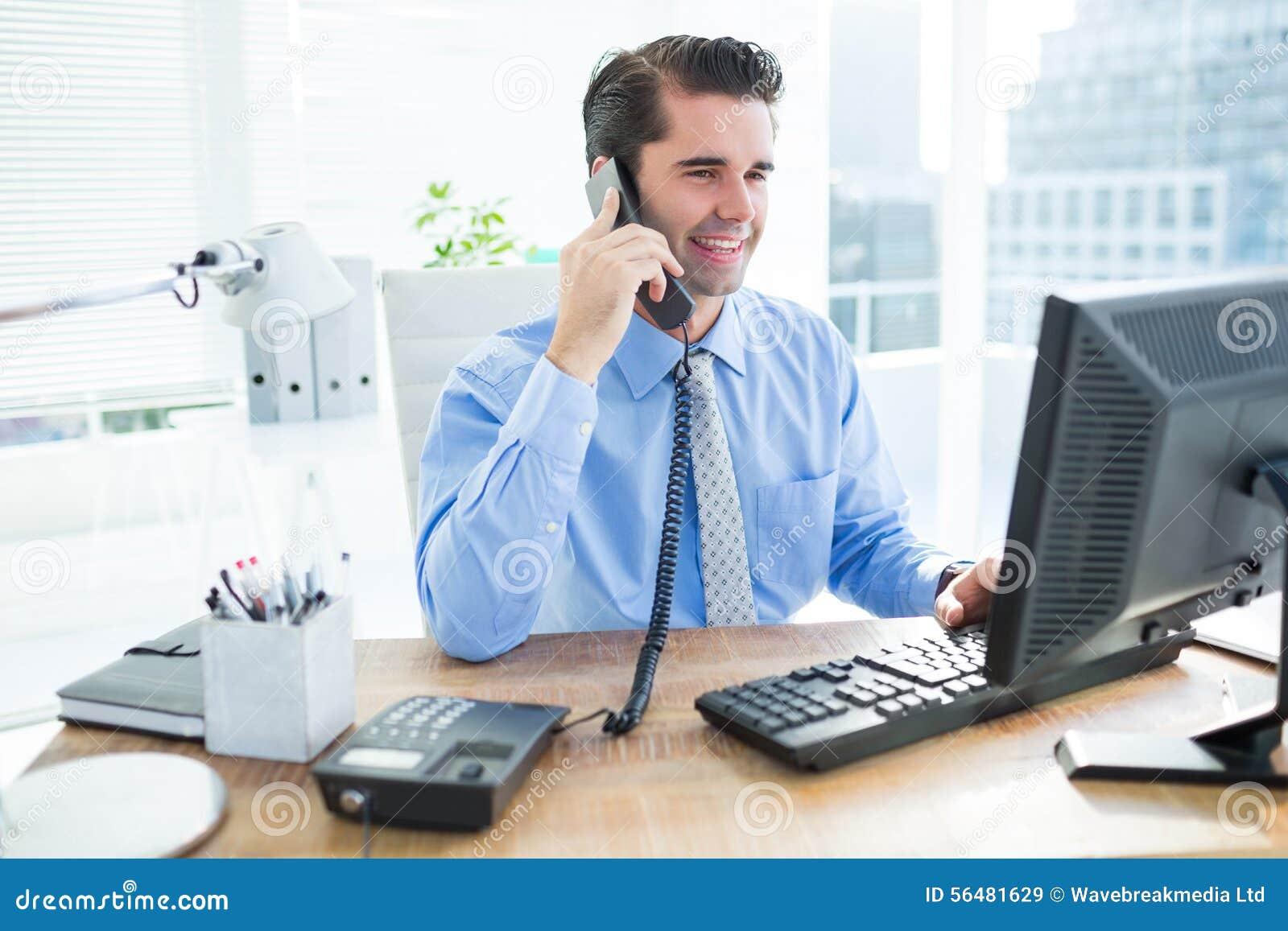 Homme d affaires de sourire utilisant son téléphoner d american national standard d ordinateur