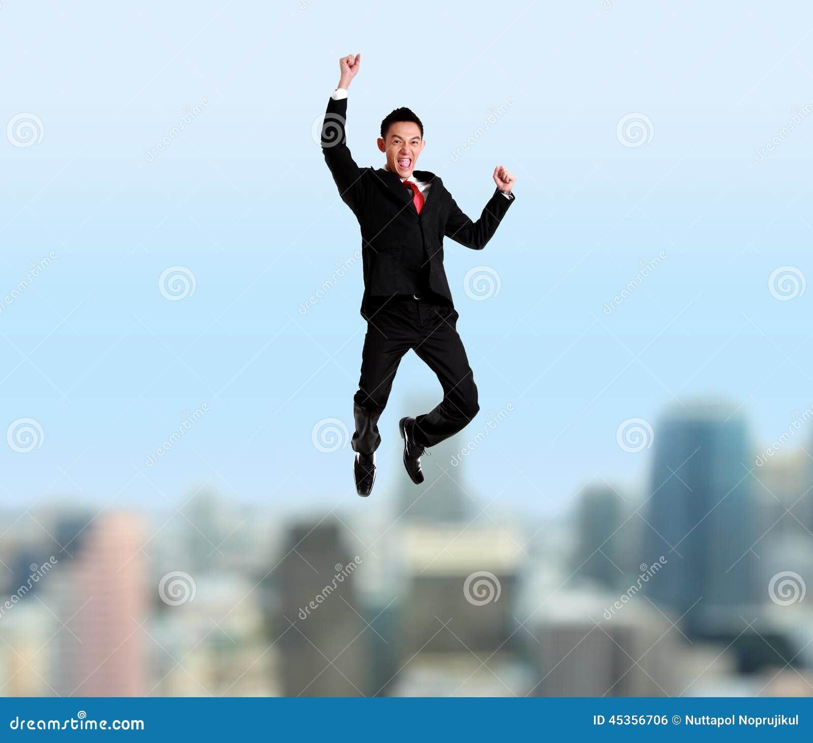 Homme d affaires de Yung sautant avec le paysage urbain sur le fond