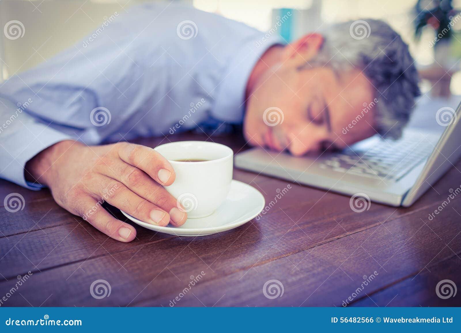 Homme d affaires dormant sur l ordinateur portable et la tasse de café émouvante