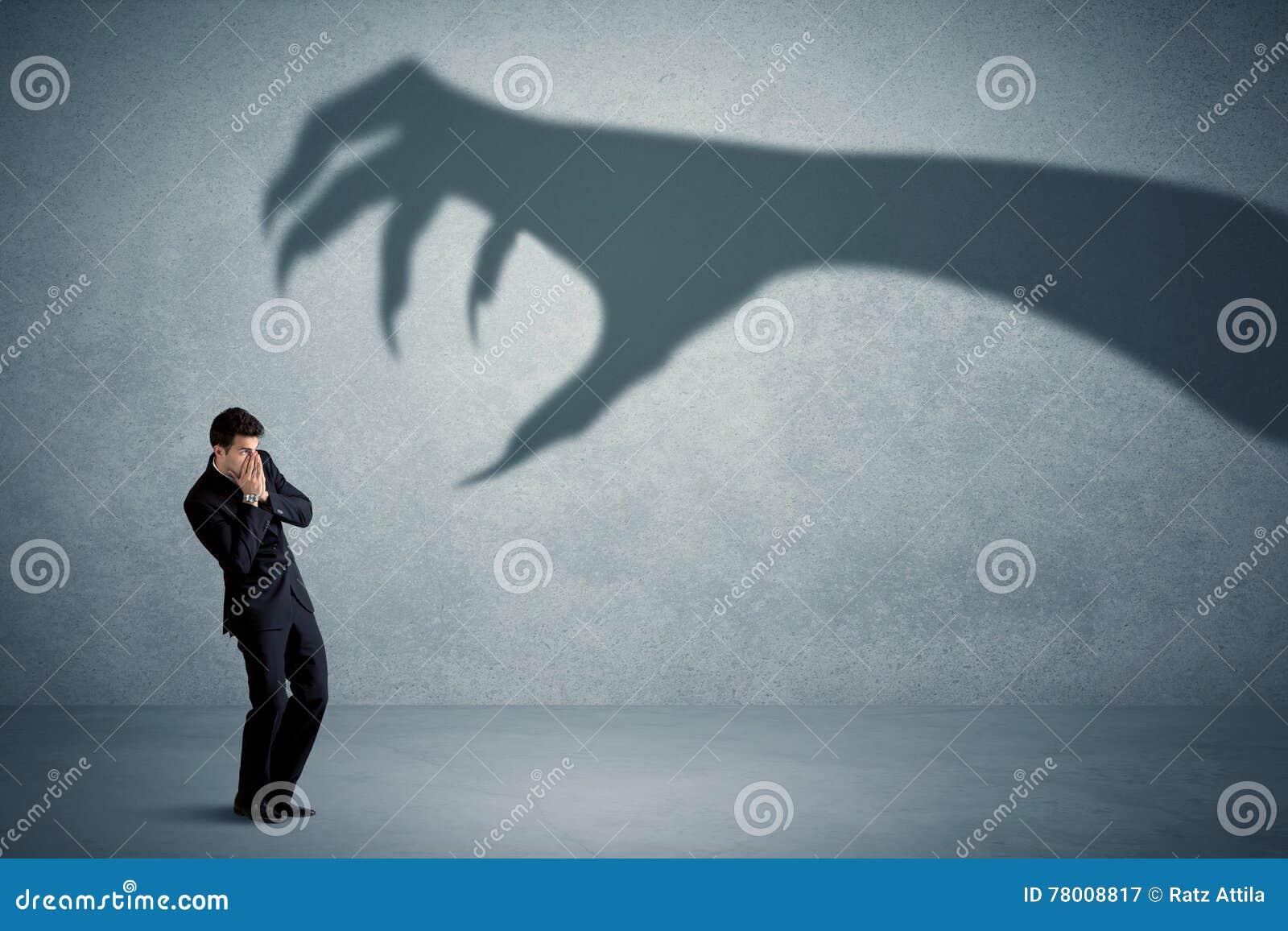 Homme d affaires effrayé d un grand concept d ombre de griffe de monstre