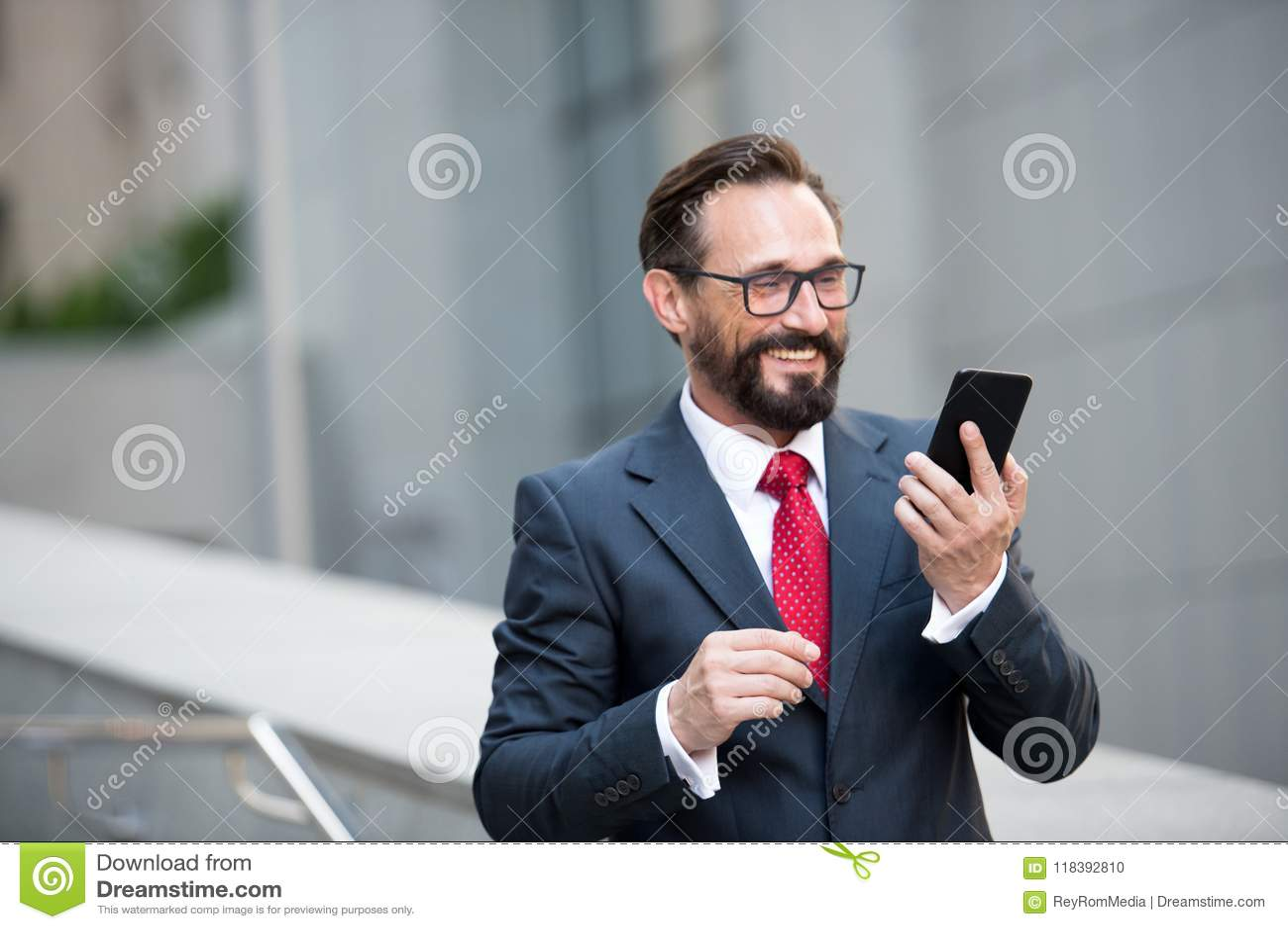 Homme d affaires en verres utilisant le téléphone intelligent sur le passage couvert de bureau avec le fond de bâtiment de ville