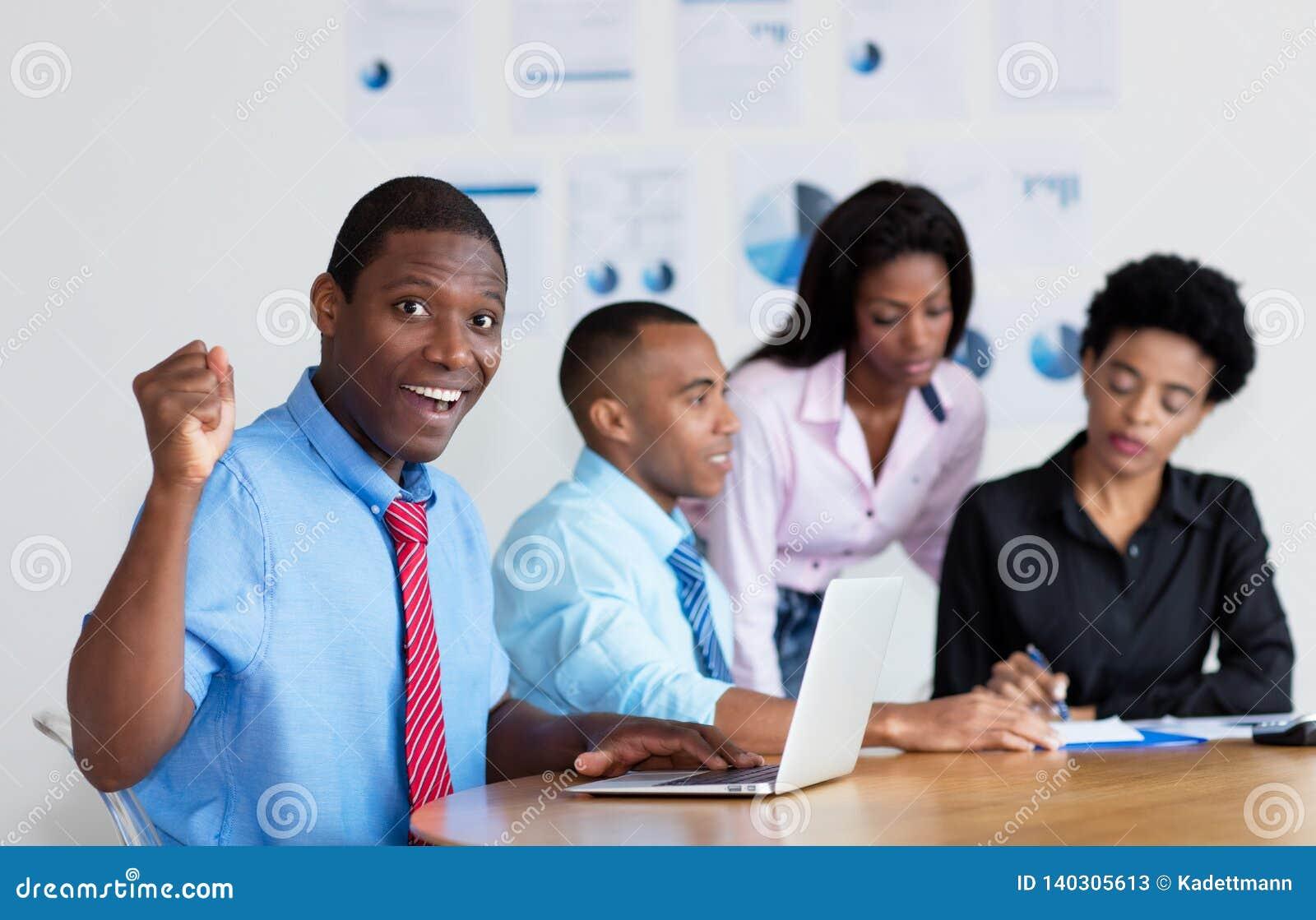 Homme d affaires encourageant d afro-américain avec l équipe d affaires au bureau