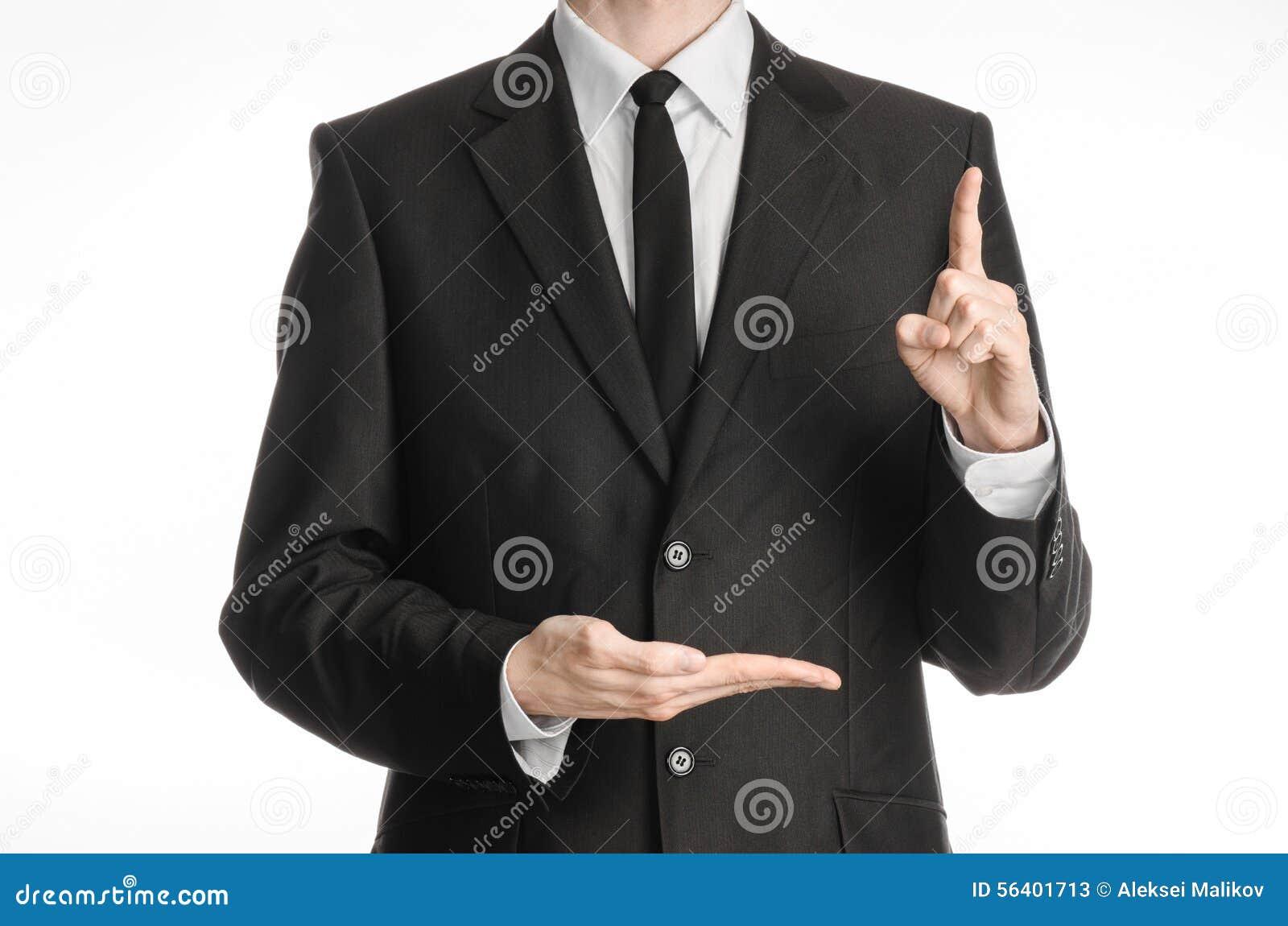 homme d 39 affaires et sujet de geste un homme dans un costume noir avec un lien montre l 39 index. Black Bedroom Furniture Sets. Home Design Ideas