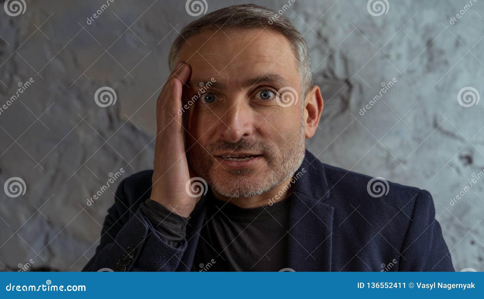 Homme d affaires frais avec la position grise de cheveux et de barbe sur le fond gris