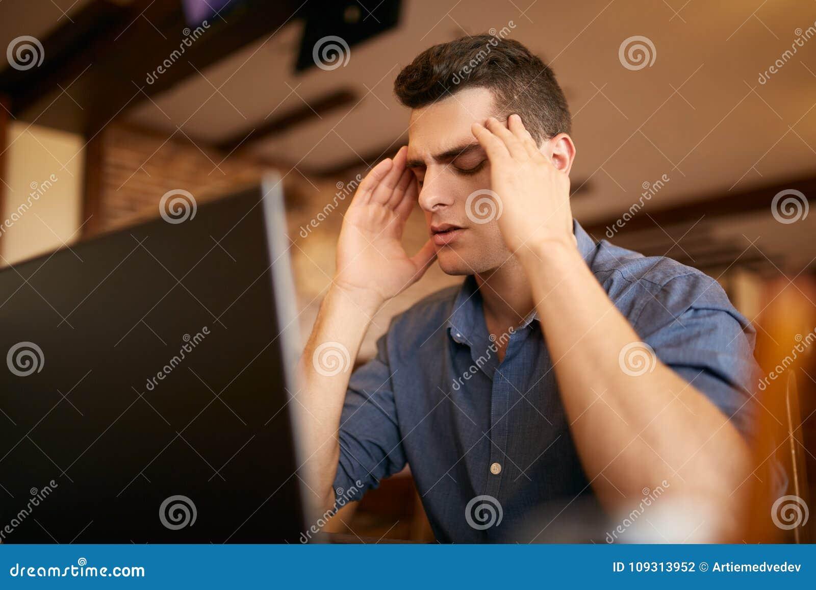 Homme d affaires frustrant sérieux avec les yeux fermés souffrant de la migraine de mal de tête sur le lieu de travail, massant d