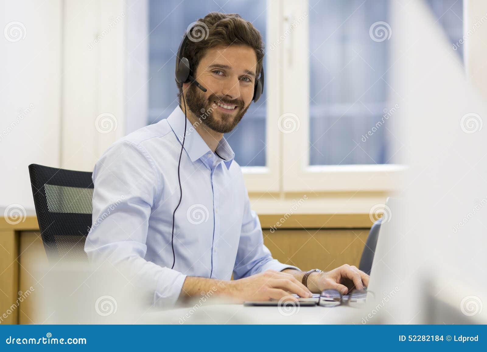 Homme d 39 affaires gai dans le bureau au t l phone casque - Skype bureau ...