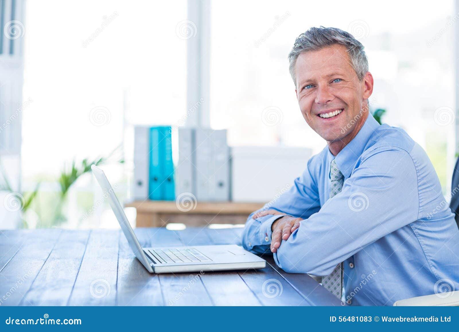Homme d affaires heureux regardant l appareil-photo avec des bras croisés