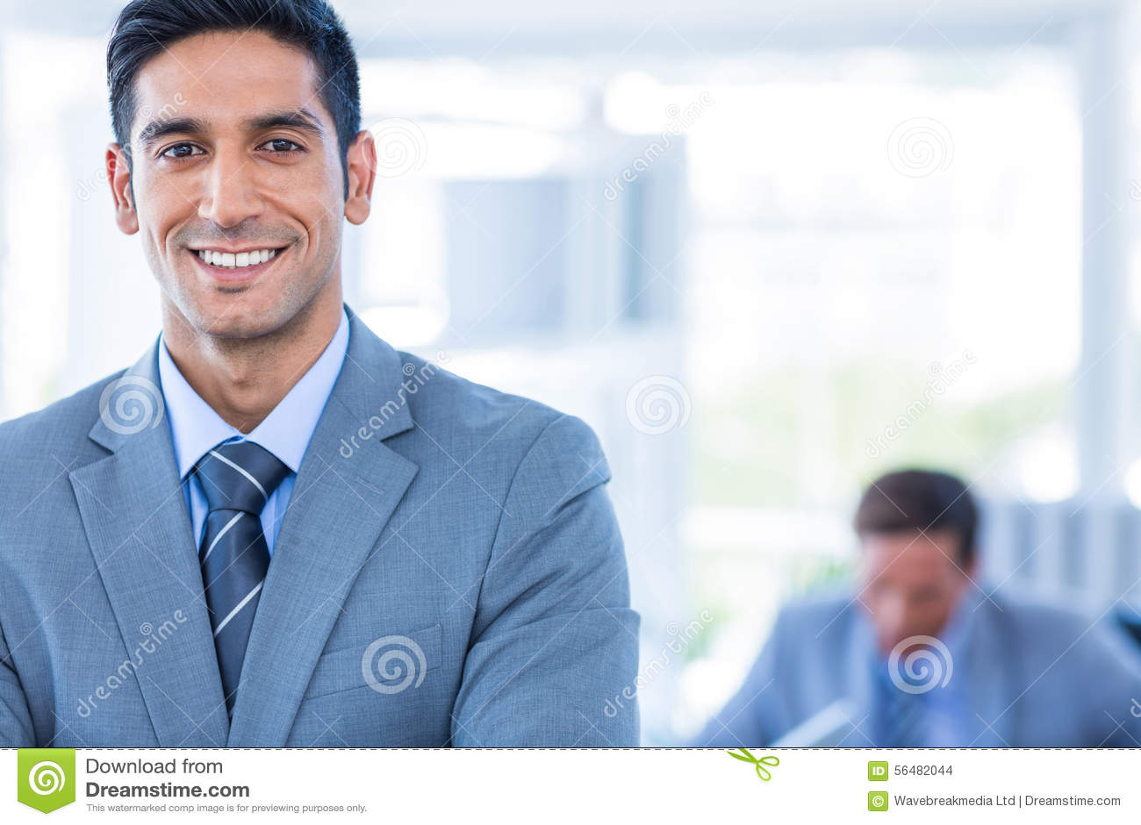 Homme d affaires heureux regardant l appareil-photo avec ses collègues derrière