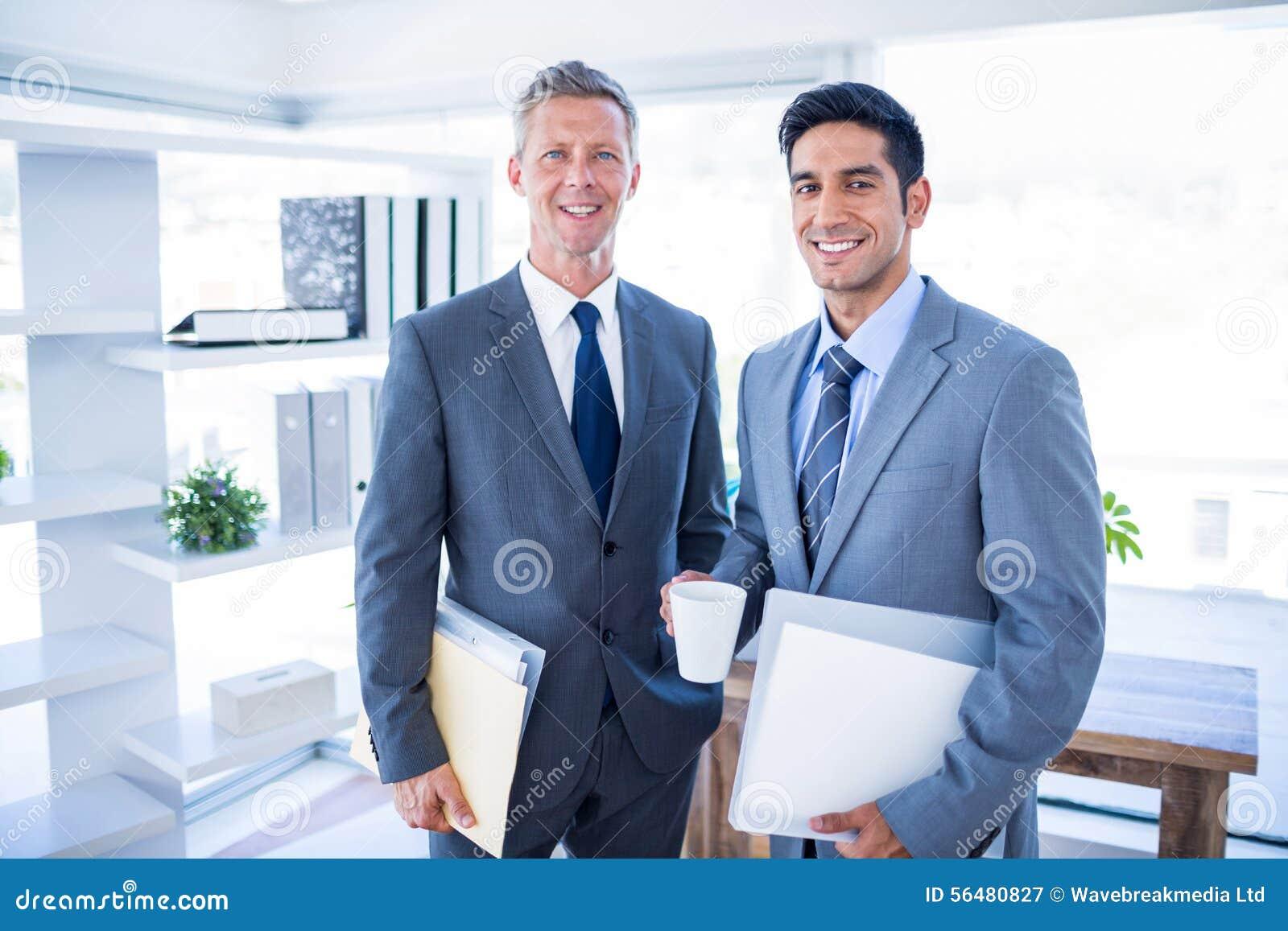 Homme d affaires heureux regardant l appareil-photo et les fichiers de recopie