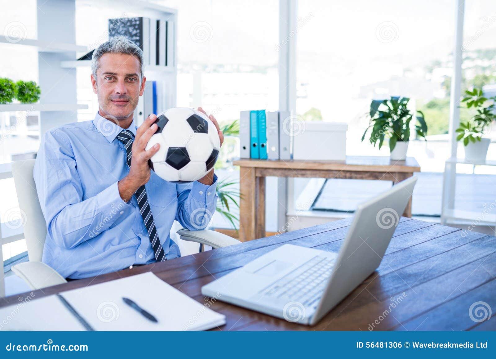 Homme d affaires heureux regardant l appareil-photo et tenant la boule de pied