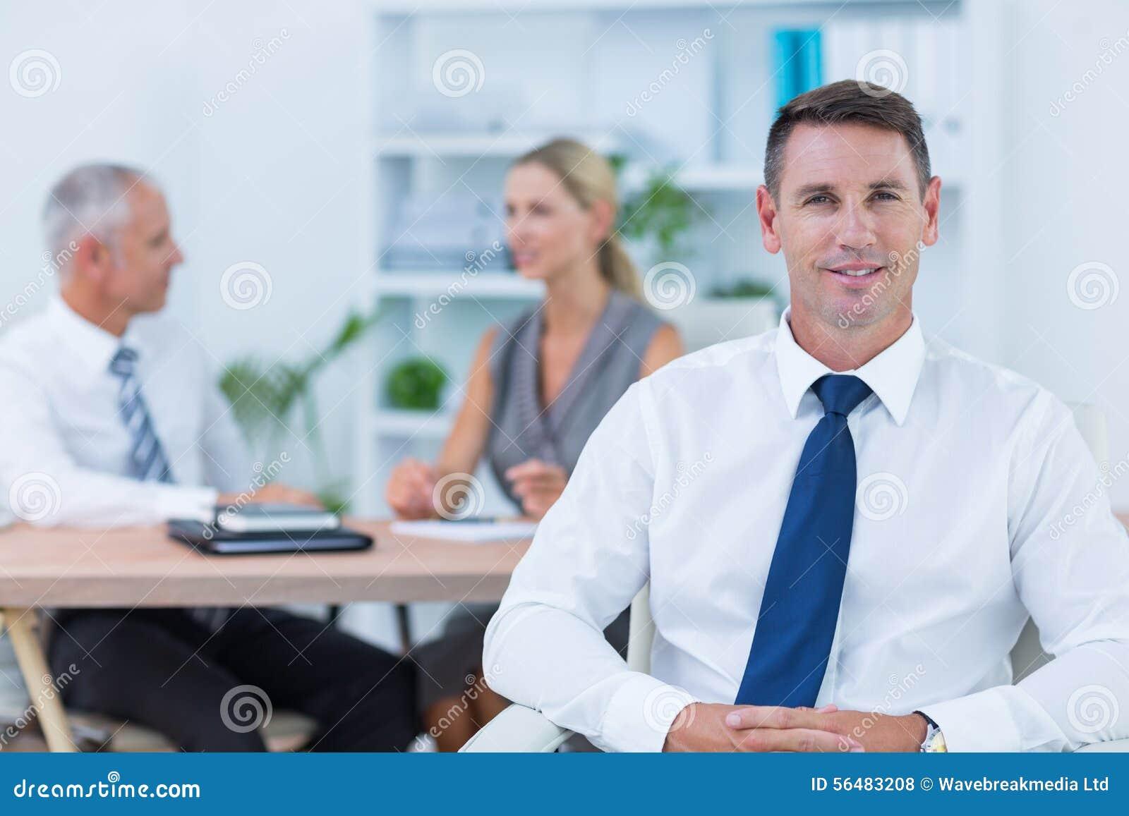 Homme d affaires heureux souriant à l appareil-photo avec des collègues derrière