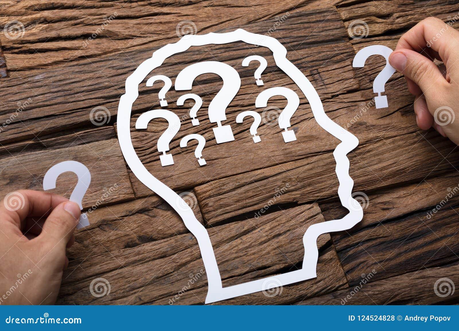 Homme d affaires Holding Question Marks par le contour principal de papier