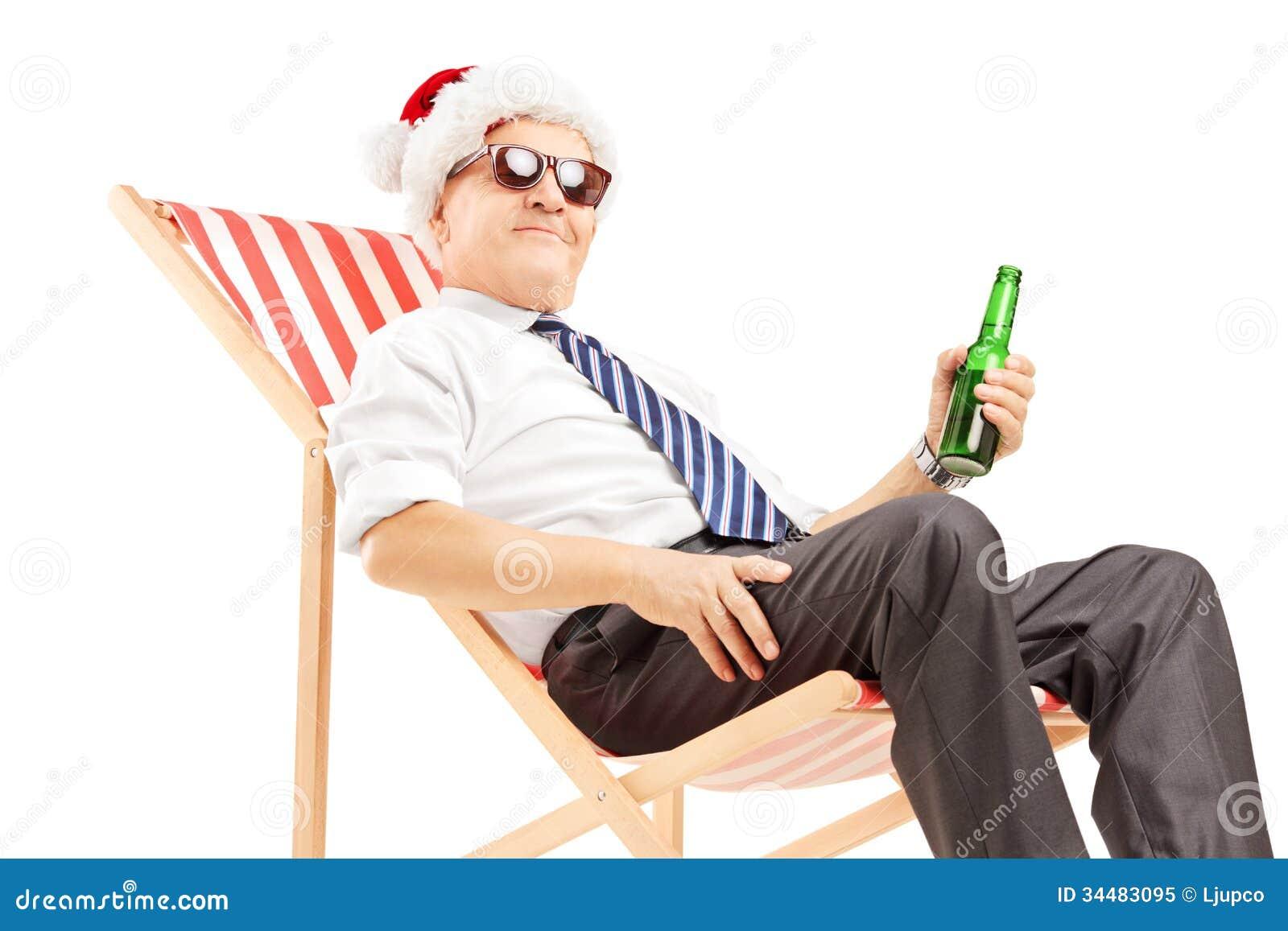 Homme d affaires mûr de sourire avec le chapeau de Santa se reposant sur une chaise et