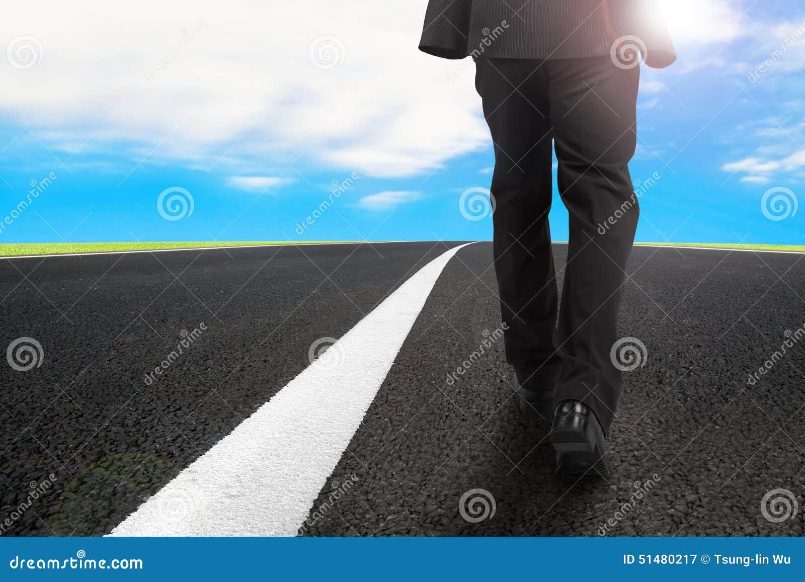 Homme d affaires marchant sur la route goudronnée avec le ciel bleu de lumière du soleil
