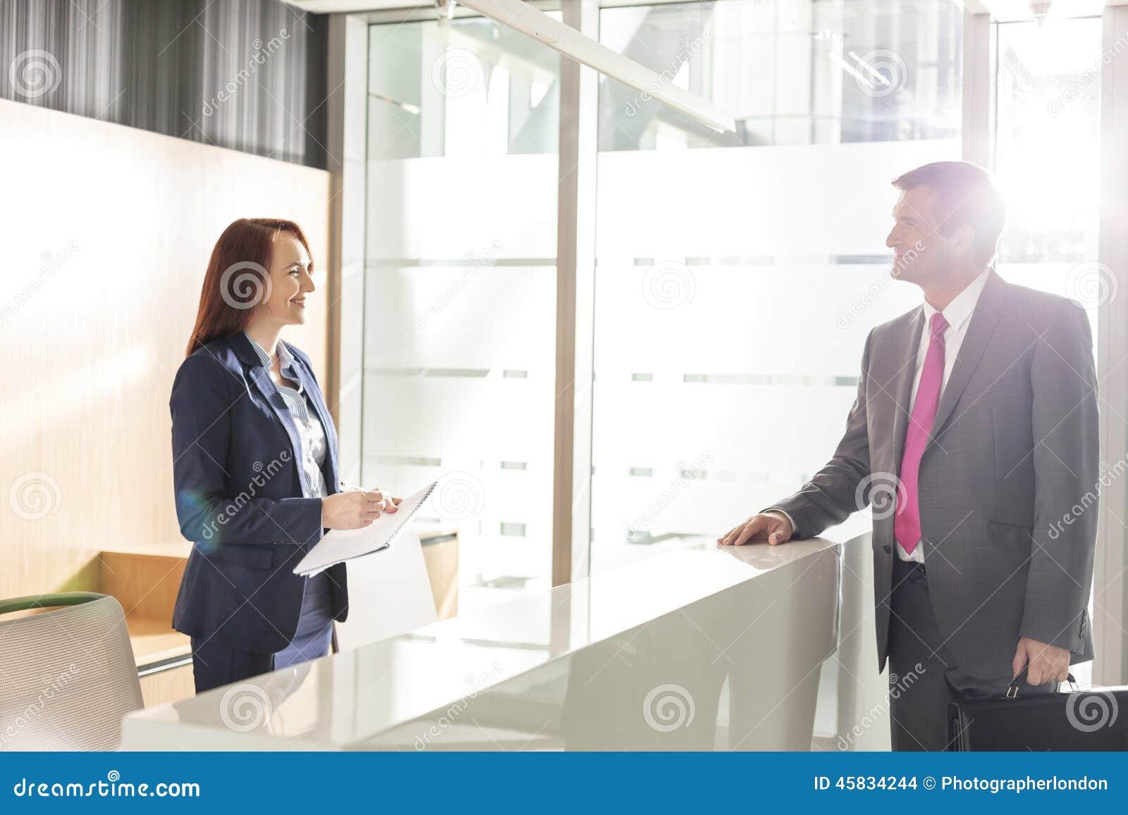 Homme daffaires parlant avec le réceptionniste dans le bureau photo